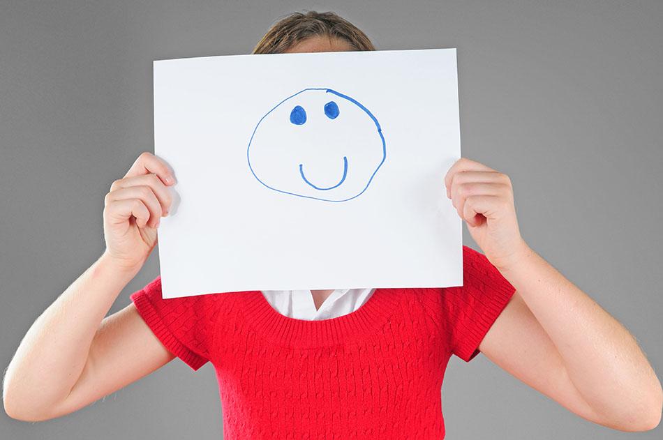 Girl hiding behind happy face